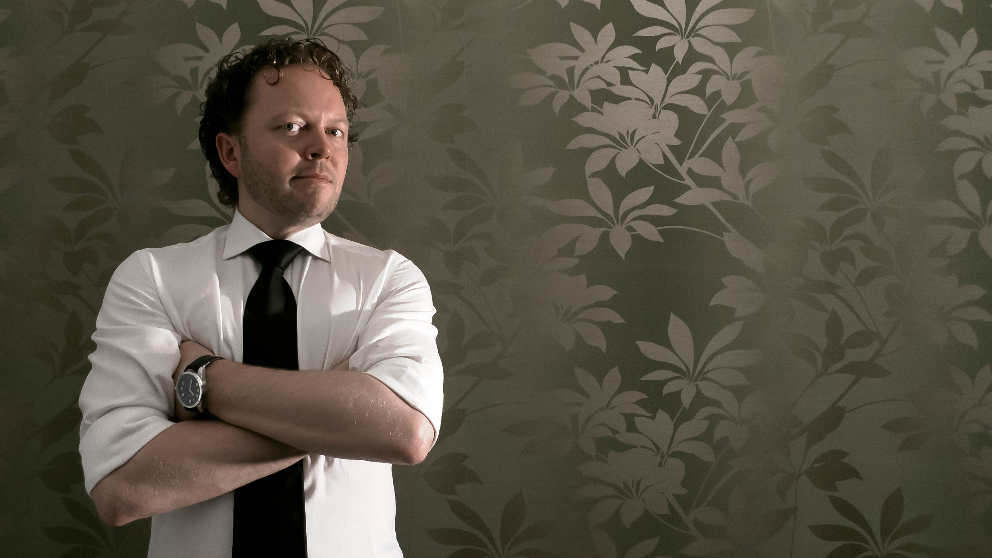 Reinier Blonk at the design studio in Amsterdam IJburg, wearing a white shirt and black tie, standing against a background of green-gold modernist flower wallpaper.